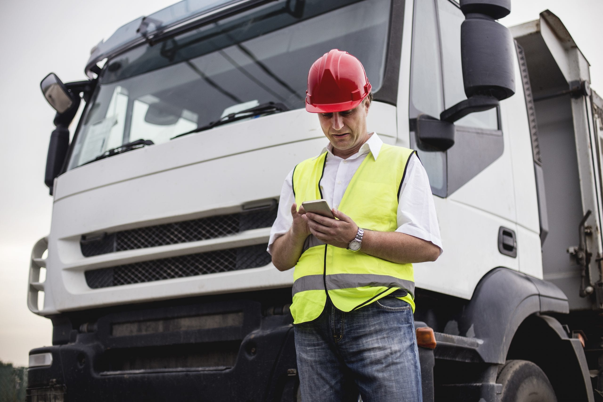 Man in red hard hat and yellow high vis vest looking at a mobile phone in front of a truck