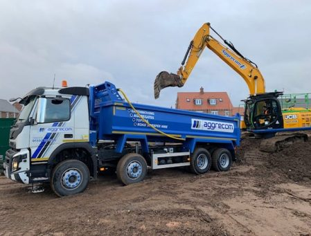 Aggrecom tipper truck with digger in background