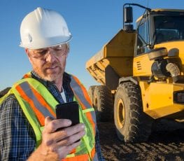 Man on construction site with tipper truck and mobile device