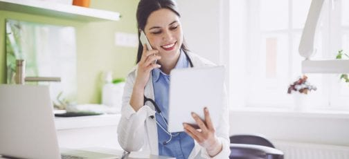 Lady doctor on telephone looking at a tablet