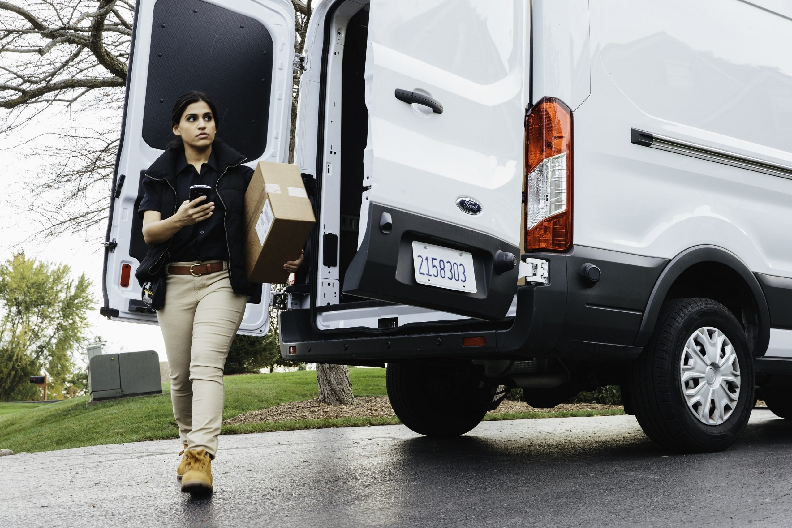 Lady delivering parcel carrying a mobile device with van in background