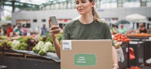 Delivery lady holding a brown box looking at mobile device